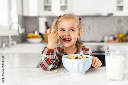 Photo Beautiful little girl having breakfast with cereal, milk and blueberry in kitche