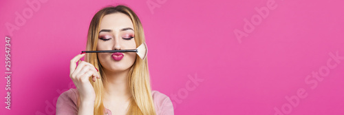Fotografía funny portrait of a beautiful young girl with makeup brush in a studio, woman fa