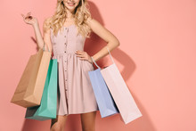 Cropped View Of Blonde Woman With Shopping Bags On Pink Background