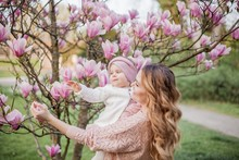 Beautiful Young Mother And Little Daughter Near The Magnolia. Spring Family Portrait.