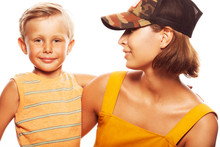 Modern Family Concept. Portrait Of Fashionable Mother With Her Gorgeous Baby Boy In Trendy Gimme Cap, Isolated On White Background. Stylish Casual Clothes. Studio Shot