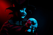Creepy Jester Woman Holding A Human Skull With Red Clown Nose.