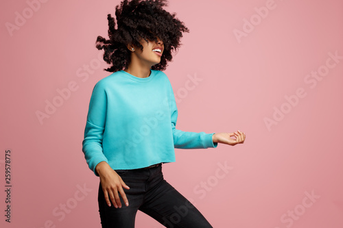 Portrait of excited african american young woman with bright smile dressed in casual clothes dance with invisible guitar over pink background. - 259578775