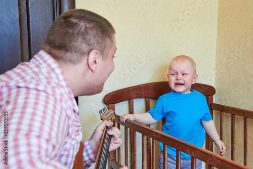 Dad plays guitar to console his crying son - Buy this stock