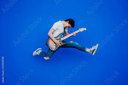 Obraz young man jumping with electric guitar on blue background - fototapety do salonu