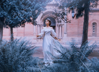 gorgeous fairy-tale princess in light white dress with open bare shoulders and full sleeves runs away from castle, girl with dark collected hair and wonderful tiara in motion, tropical green nature