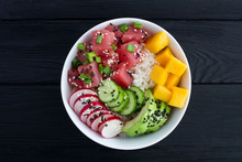Poke Bowl With Tuna In The White Bowl In The Center Of The Black Wooden Background.Top View.Closeup.
