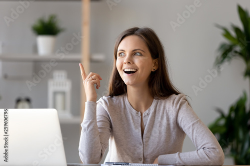 Obraz na plátne Young woman sitting at desk feels excited with good idea