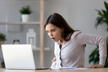 Shocked Woman Looking At Laptop Screen Surprised With Bad News