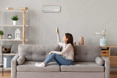 Young smiling woman sitting on couch switching on air conditioner Canvas Print