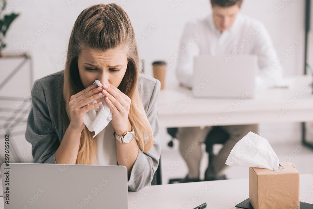 Fototapeta blonde businesswoman sneezing in tissue near coworker in office