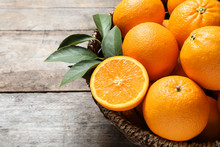 Wicker Bowl With Ripe Oranges On Wooden Background, Closeup. Space For Text