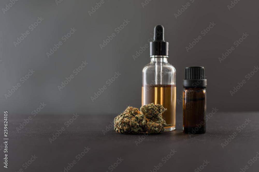 Photo  Medizinisches Cannabis und Cannabis Öl in Fläschchen grauer Hintergrund