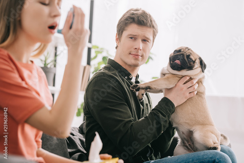 Photo selective focus of handsome man holding cute pug and looking at girl allergic to