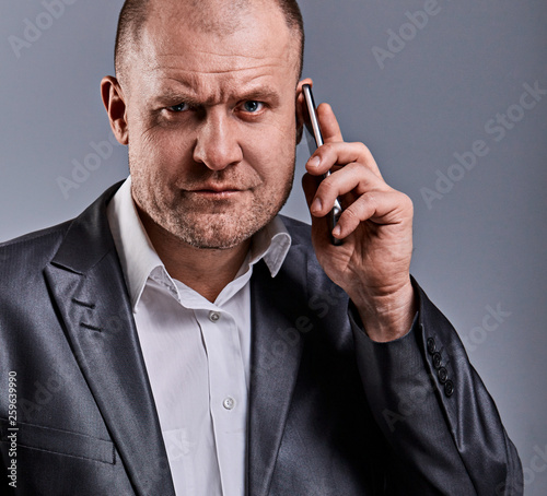 Unhappy tired angry business man talking on mobile phone and holding in hand one more phone in office suit on grey studio background Fototapet