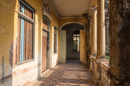 Foto op Plexiglas Barcelona Passage with tiled floor and boarded-up windows along columns on the second floor of the Mansion or Villa Bodega, a half-ruined colonial-era building (1910-1920s) in Phnom Penh city center, Cambodia.