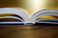Opened Book On A Golden Background. Close-up
