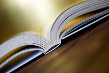 Opened Book Is Lying On The Boards On A Golden Background. Close-up