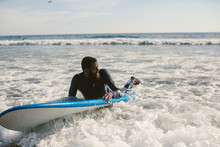 Handsome Man Has Surfing On Small Waves. Mixed Race Dark Skin And Beard. Summer Sport Activity, White Wash Waves