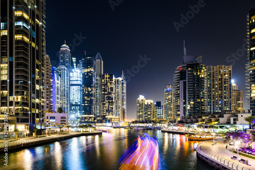 Fototapety, obrazy: Stunning view of the Dubai Marina at dusk with illuminated skyscrapers in the background and a light trails left by a yacht sailing in the foreground. Dubai, United Arab, Emirates.