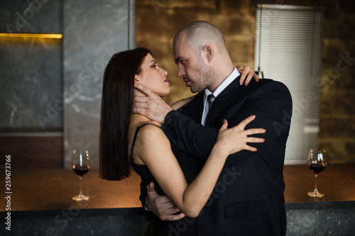 Obraz na plátně  A bald man strangles a dark-haired girl in a long dress in a restaurant with his hands
