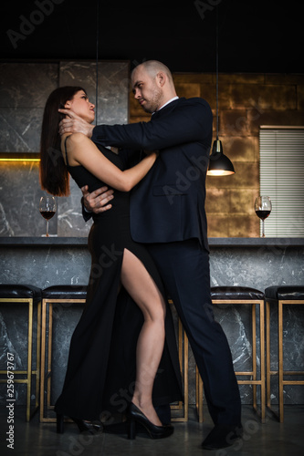 A bald man strangles a dark-haired girl in a long dress in a restaurant with his hands Slika na platnu