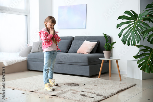 Obraz Little girl in muddy shoes messing up carpet at home - fototapety do salonu