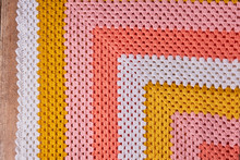 Needlework. Colorful Woolen Crocheted Bedspread On A Wooden Background. Close-up.