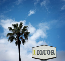 Aged And Worn Liquor Store Sihn And Palm Tree