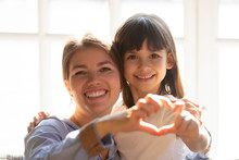 Headshot Portrait Mother And Daughter Make Heart Shape With Hands