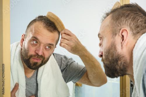 Fotografia, Obraz  Man using comb in bathroom