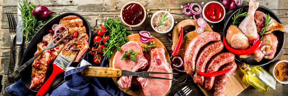 Fototapety, obrazy: Various raw meat ready for grill and bbq, with vegetables, greens, sauces kitchen grilling utensils. Chicken legs, pork steaks, sausages, beef ribs with herbs, rustic wooden background copy space