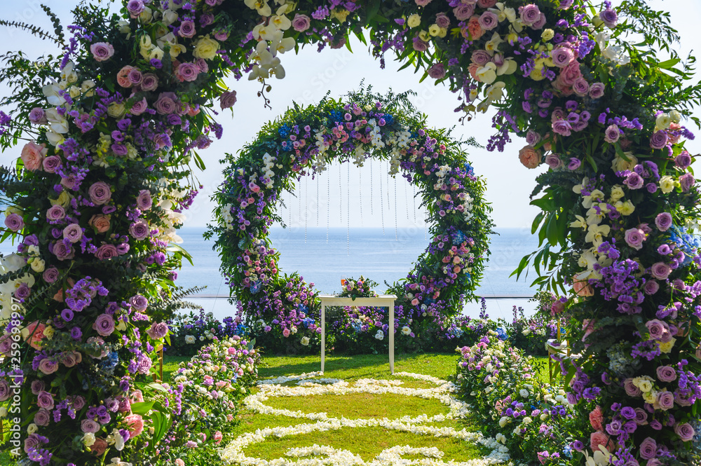 Fototapeta Wedding ceremony. Arch, decorated with flowers on the lawn, beach background, sea in summer.