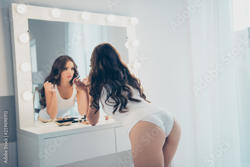 Rear back behind view portrait of her she nice-looking winsome attractive lovely well-groomed perfect slim fit thin wavy-haired lady applying facial cosmetics in light white interior room