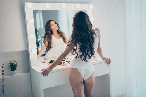 Rear back behind view portrait of her she nice-looking adorable shine attractive lovely well-groomed perfect slim fit thin wavy-haired lady standing in front of mirror in light white interior room