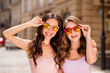 Close up portrait of attractive dreamy sweet ladies students have trip long hair free time colorful touch specs travelling feel satisfied excited enjoy dressed in pastel clothing center outdoors