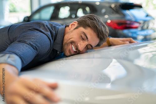 Young man hugging new car - 259708789