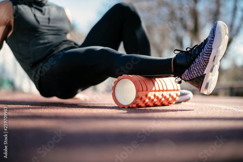 Fotografie, Obraz  Man foam rolling. Athlete stretches using foam roller.