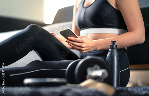 Online workout course, personal trainer service or fitness app in phone. Fit woman using smartphone while working out at home. Gym, coach or health application on internet. Lady looking at cellphone.