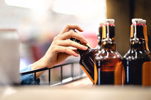 Hand Taking Bottle Of Beer From Shelf In Alcohol And Liquor Store. Customer Buying Cider Or Supermarket Staff Filling And Stocking Shelves. Retail Worker Working. Woman Choosing Lager Or Pale Ale.