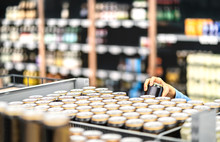 Retail Worker Filling Shelf With Drinks In Grocery Store Or Customer Taking Can Of Beer Or Soda. Staff At Supermarket Stocking Shelf With Alcohol Or Doing Inventory. Woman Buying Liquor In Shop.