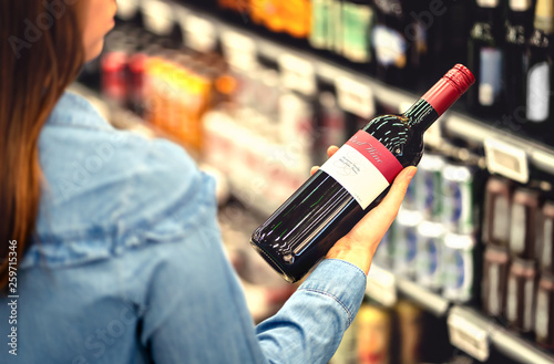Canvas Prints Bar Woman reading the label of red wine bottle in liquor store or alcohol section of supermarket. Shelf full of alcoholic beverages. Female customer holding and choosing a bottle of merlot or sangiovese.
