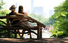 Couple Sitting On A Park Bench And Having A Romantic First Date. Lovers With Romance And Trust. Back View Of Happy Man And Woman Watching The Buildings In Manhattan, New York City From Central Park.