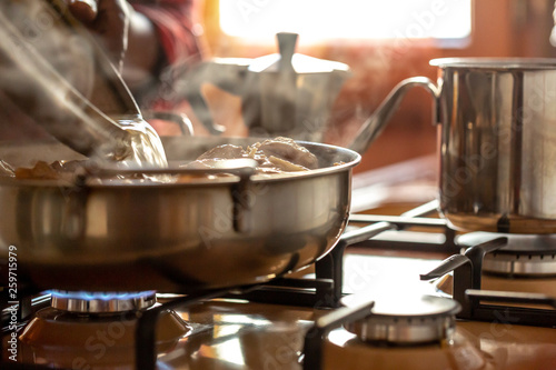 Closeup view of silver pots and pans cooking food a stovetop