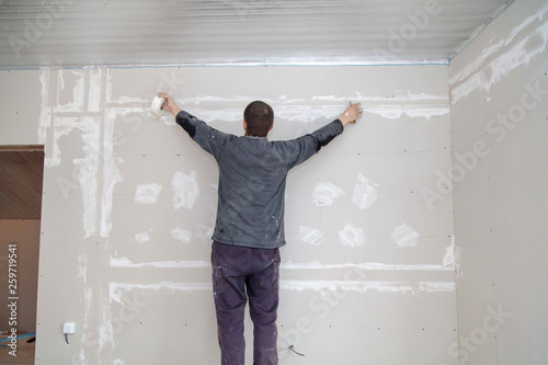 Worker aligns the walls with plaster  Repair in the house