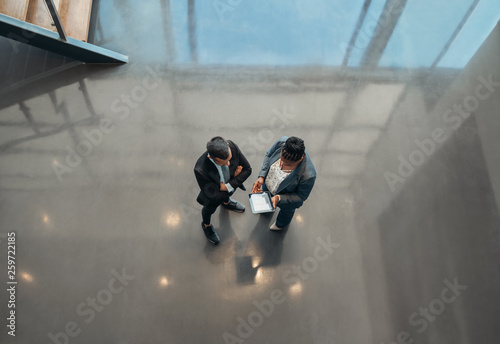 Two business people standing in the open spaced lobby of an office looking at a Canvas Print