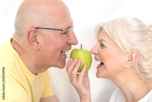 Fototapeta Senior couple with apple, healthy teeth concept obraz