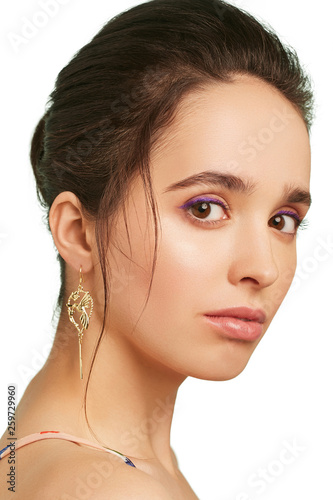 Closeup portrait of a pretty lady with lilac eyeshadows and dark brown hair, wearing stylish long earrings Fototapet