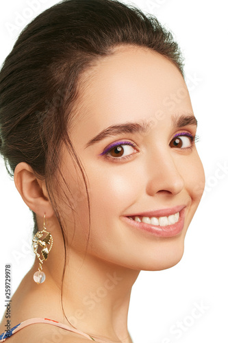 Fototapeta  Closeup portrait of a smiling lady with lilac eyeshadows and tied back hair, wearing long dangle earrings