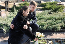 Couple Putting Flowers On Grave Of Their Relative At Funeral